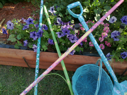 Even when left lying about, these colorful garden tools add cheerfulness to your back yard landscape.