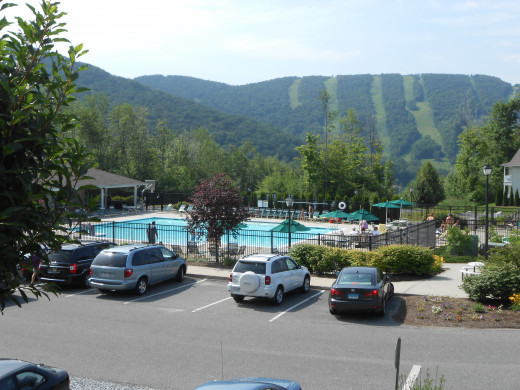 The Outdoor Pool of Vacation Village with Jiminey Peak in the background. It's a beautiful view that visitors can enjoy while keeping cool.