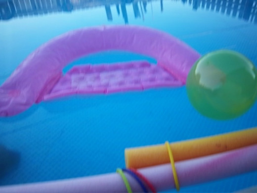 Image of an above ground pool with colorful flotation toys.