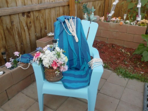 Image of blue striped hammock thrown over blue lawn chair with basket of flowers.