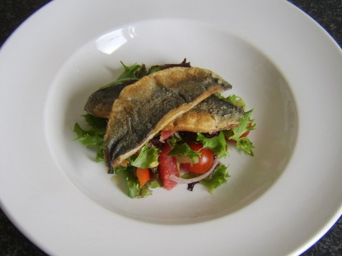Crispy skinned fried herring fillets are served on a bed of red grapefruit salad