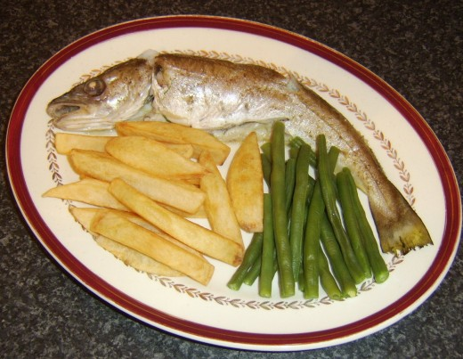 Chips and green beans are plated alongside whiting