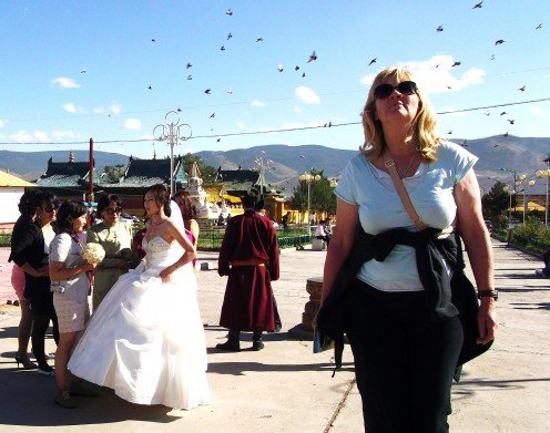 A bride and her maids preparing for photos at the monastery. Note the traditionally dressed man in the background.