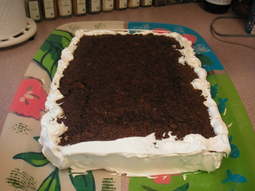 When the cake is completely cooled, begin icing the edges