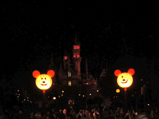 View of the castle from Main Street. The castle is decorated in orange and purple lights and is framed by two gigantic Mickey pumpkin heads!