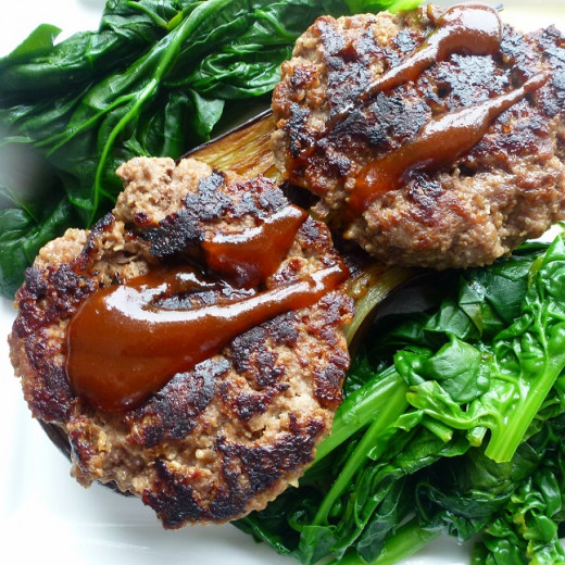 Nice combination of meat patties on a bed of eggplant, with spinach and plum sauce.