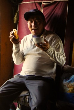 After a long day's at the wheel, our driver, Bagi, enjoys a bowl of warm yak's milk and a chunk of delicous nomad bread