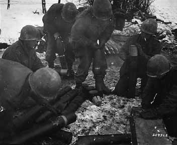 Crew in the 591st FAB preparing the shells for firing. Gotta love the GI with the cigarette next to all that powder.