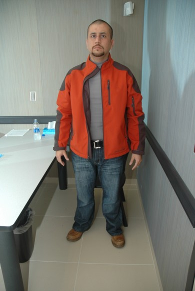 ZIMMERMAN'S UNZIPPED JACKET IN PHOTO TAKEN AT THE SANFORD POLICE STATION