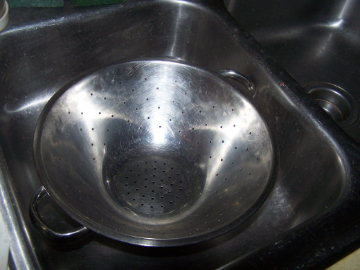 I prefer to use a stainless steel strainer, although you could use a plastic one or one made from screen.