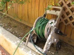 Rubber garden hose in its wheel house storage.
