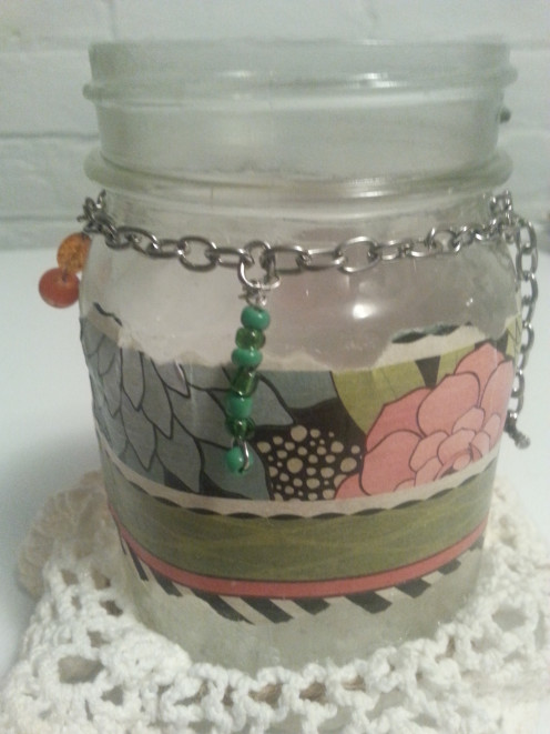 Using jewelry beads and wire, create dangling ornaments of varying lengths to attach to the chain around the jar.