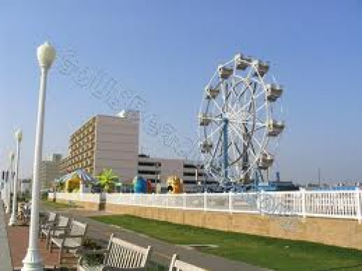 A Ferris wheel sits along the edge of the beach for everyone to enjoy during the day or night in Virginia Beach, Virginia.