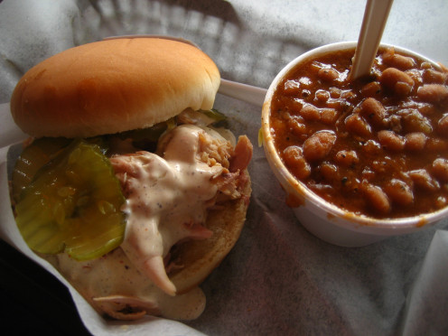 A barbecue chicken sandwich topped by Alabama White Sauce