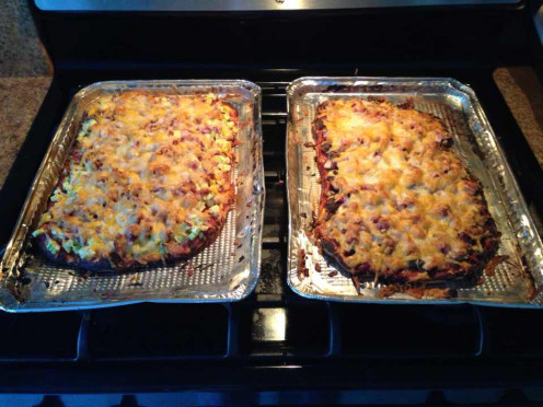 Pizzas - both have tomato paste, apple smoked bacon, red onions, and four cheeses (Mozarella, Monterey Jack, Cheddar, Parmesan). Left one has zucchini, while right one has crimini mushrooms