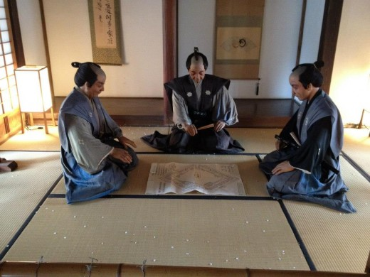 Replicas of feudal lords engaged in war strategy discussions in Honmaru Goten