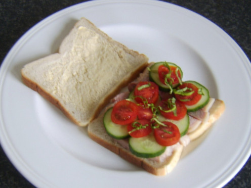 Cherry tomatoes, cucumber and basil complement a simple ham sandwich