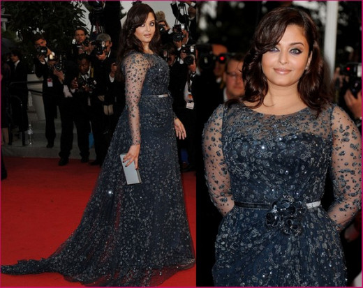 Aishwarya Rai in a strapless glittering gray-blue gown with a sheer embellished long-sleeve overlay and long train. She tried to hide her chubby arms but failed miserably. .