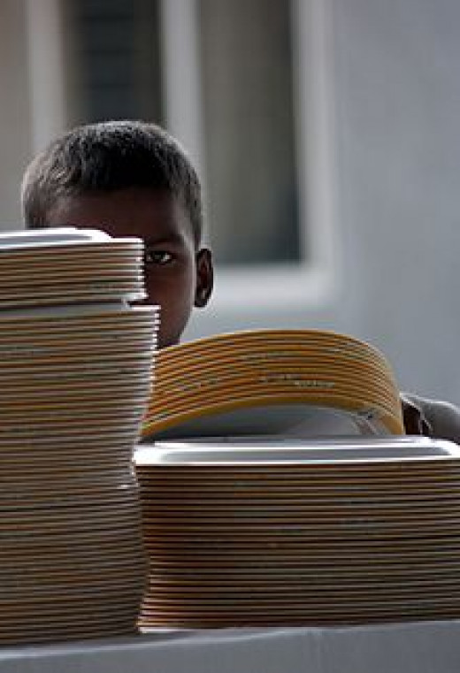 Young boy stacking plates in Bangalore. India