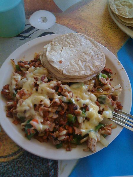 "A plate of ""alambre"", a mexican cuisine dish consisting of meat, cheese, peppers, bacon and other"