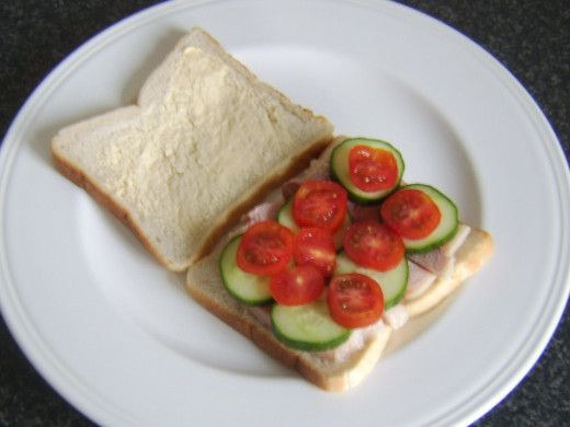 Slices of cucumber and tomato are laid on top of ham