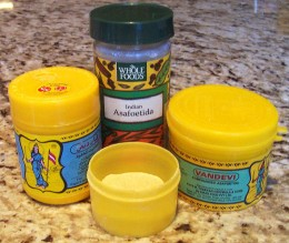 "Jars of asafoetida powder (a.k.a. ""hing"", ""yellow powder"") available commercially."