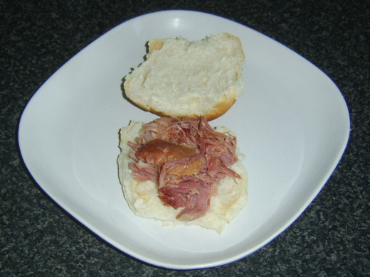 Shredded roast ham is laid on the bottom half of a sliced open roll