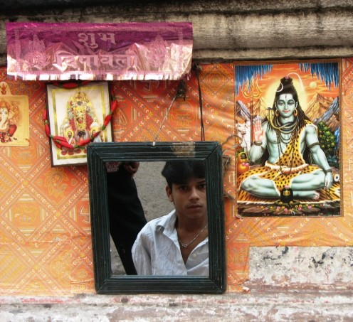 Youth staring at his friend through mirror of a way-side saloon.