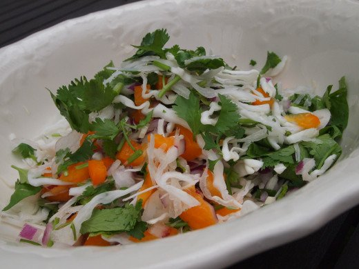 Prepare the red onion, cabbage, orange bell pepper and cilantro (coriander) leaves as indicated and mix them together in a bowl.