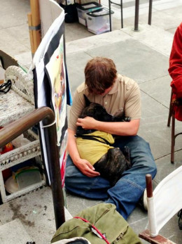 A tired protester embraces the Mailman's best friend.