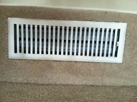 An old air conditioning register is spray painted white to look brand new.