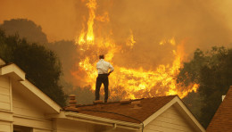 Resident stands on rooftop as fire in California moves closer to his home.
