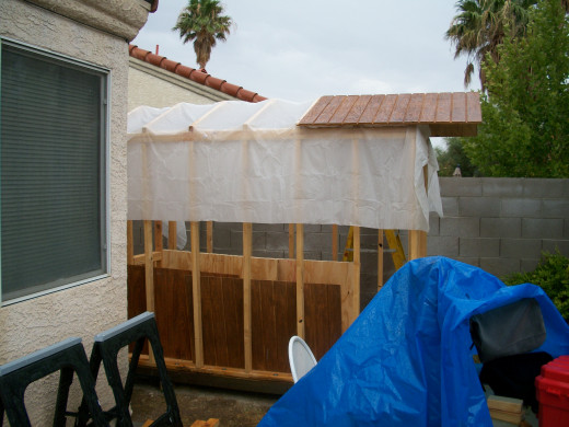 A sheet of plastic protects the wall frames and floor while the roof decking is installed. Most of the plastic remains underneath for extra moisture protection.