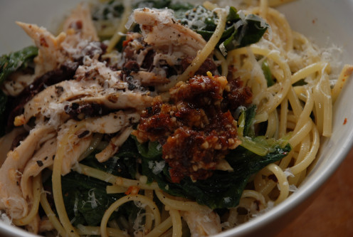 Linguine topped with sun-dried tomato pesto, escarole, olives, and shredded chicken.