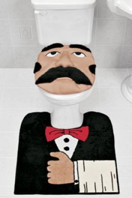 "By Jove! ""Butler"" toilet/bath set adds luxury to your lavatory! Keep the area around your toilet tidy with this whimsical two-piece set. Plush seat cover (17"" x 15"") and slip-resistant rug (24"" sq.) feature a mustachioed manservant properly dressed i"