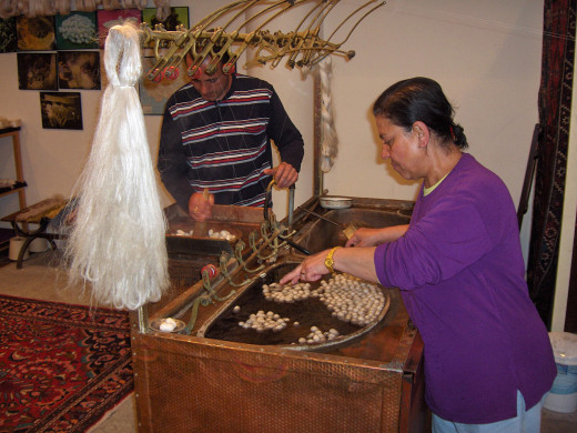 Silk filaments unraveled from silk cocoons; Hadosan, Urgüp, Cappadocia, Turkey. The woman is picking filaments from cocoons and feeding them into the reeling machine. Many filaments from different cocoons are combined into one thread.