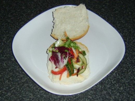 Salad bed is arranged on bread roll