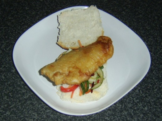Battered pollack fillet is laid on salad bed
