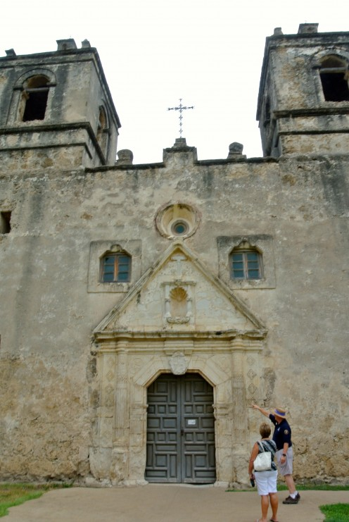 A docent guides a visitor at the church at Mission Concepcion