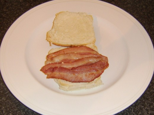 Bacon is laid on bottom of bread roll