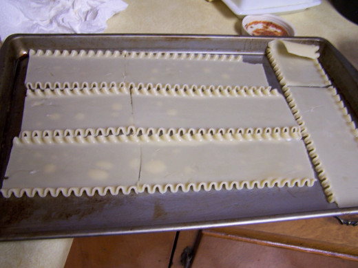 Cooked noodles flat on a tray to allow to cool.
