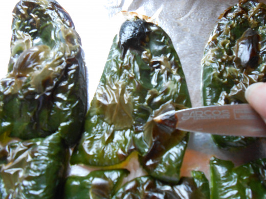 Use a sharp paring knife or just your fingers to remove the skin of the pepper.