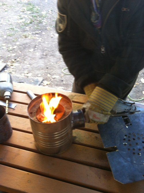 Adding small wood fuel into the combustion chamber through the fuel feed inlet.