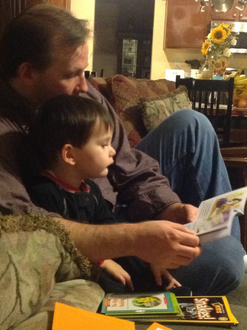 Exhausted father still makes time for reading before bedtime.