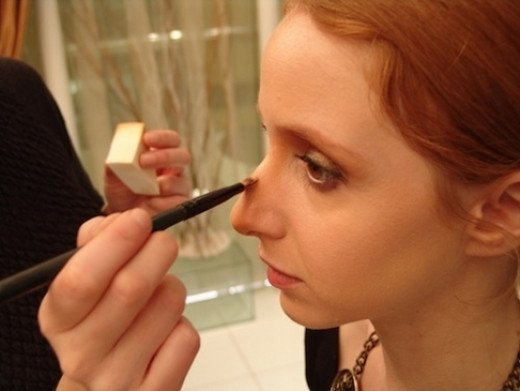 If going under the knife is not for you, consider going under some paint.  It requires a lot of makeup, but you can create a blend of shadows and bright areas that will give the impression of a narrower, straighter nose