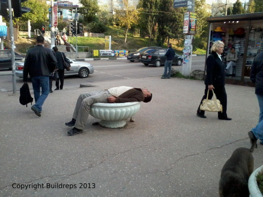 This amazing picture is taken at Sep 26th, 2013 in Crimea. I just came back from shopping when I saw this man lying in the middle of this planter. The public is used to this kind of intoxication.