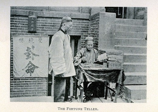 A Chinese Fortune Teller plies his trade on the sidewalk, 1923