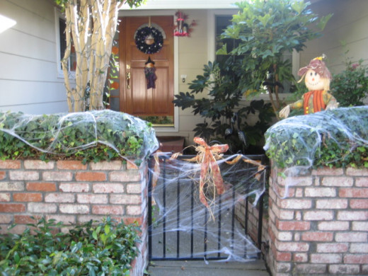 A combination of pretty and scary add to this Halloween scene with an entrance adorned in bows and spider webs.