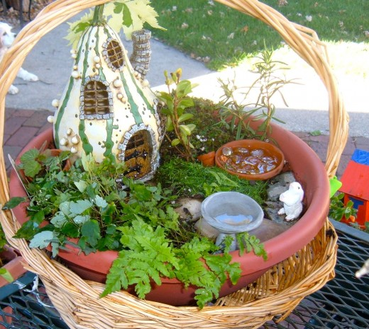 This basket garden uses a plastic circular pot to hold a Fairy house, pool, path and miniature bird bath.