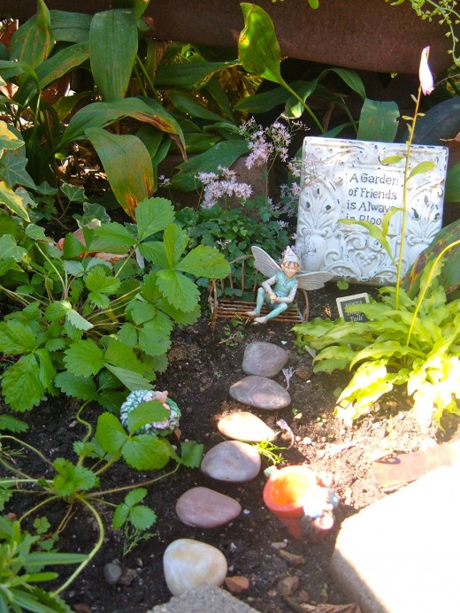 Here is a prefab stone path that leads us to a bench with a fairy, and a garden verse.